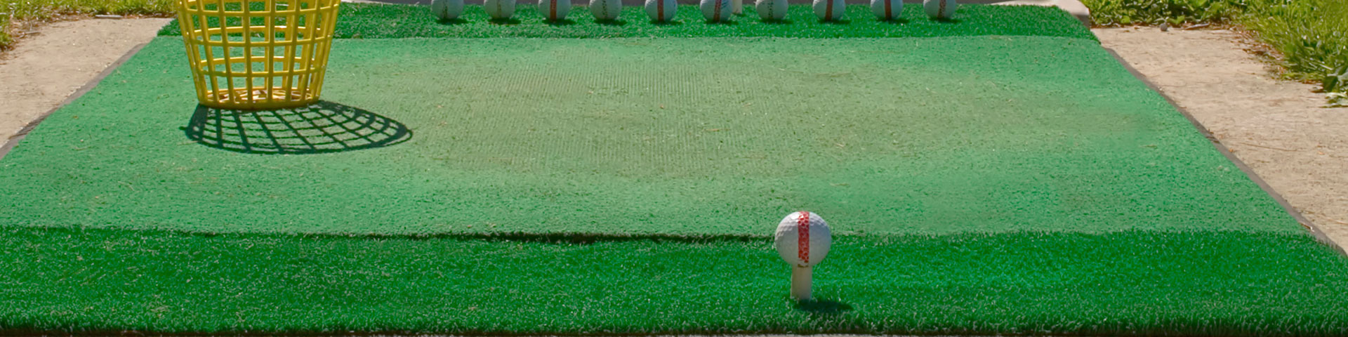A golf ball sits on a tee at a driving range